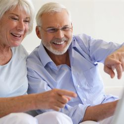 Couple de seniors souriants devant une webcam